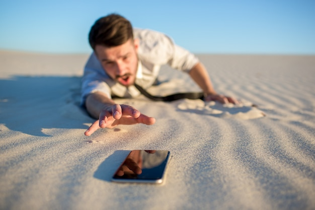 Słaby sygnał. biznesmen szuka sygnału telefonu komórkowego na pustyni