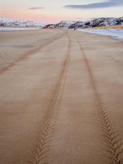 Ślad bieżnika opony na morskim piasku sięgający w dal.