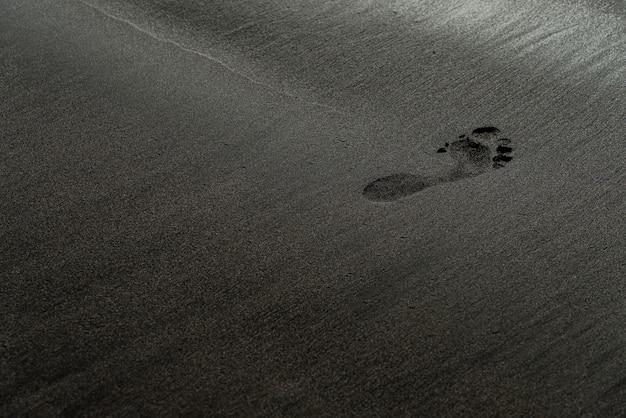 Ślad na fotografii makro z czarnym piaskiem. ludzki ślad na jedwabistej czerni tekstury plaży o płytkiej głębi ostrości. minimalistyczne czarne tło. teneryfa piaszczysty brzeg wulkaniczny.