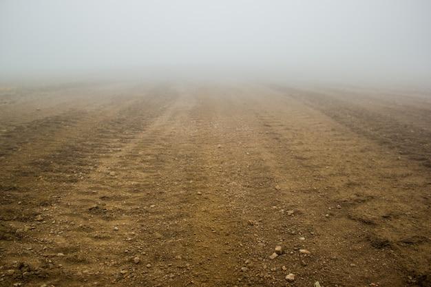 Ślad opon na brunatnej glebie.