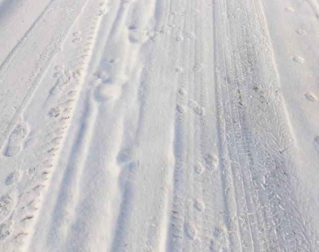 Ślady kół pojazdu na zaśnieżonej drodze. sfotografowany z bliska.
