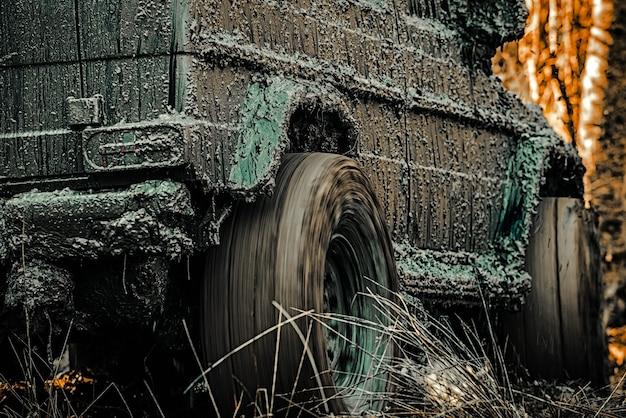 Ślady na błotnistej wyprawie terenowej widok z dołu offroadera na duże koło samochodu terenowego na wiejskiej drodze i ...