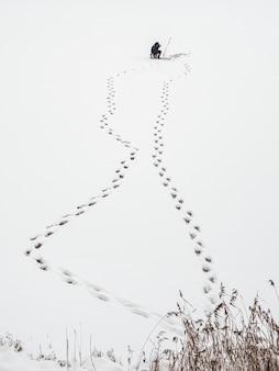 Ślady na śniegu sylwetka rybaka na jeziorze pokryte śniegiem