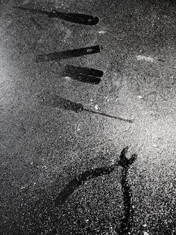 Ślady narzędzi na czarnym stole posypanym białym pyłem