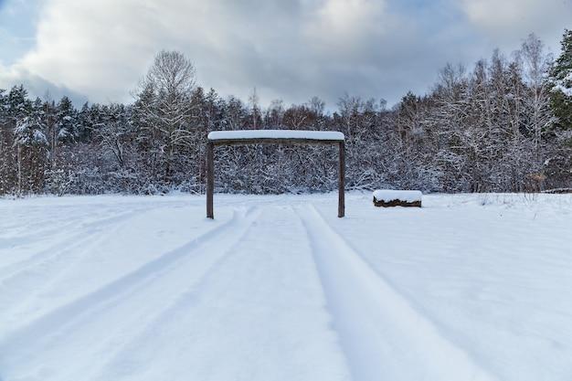 Ślady od kół maszyny po śnieg, zimowy krajobraz na polanie