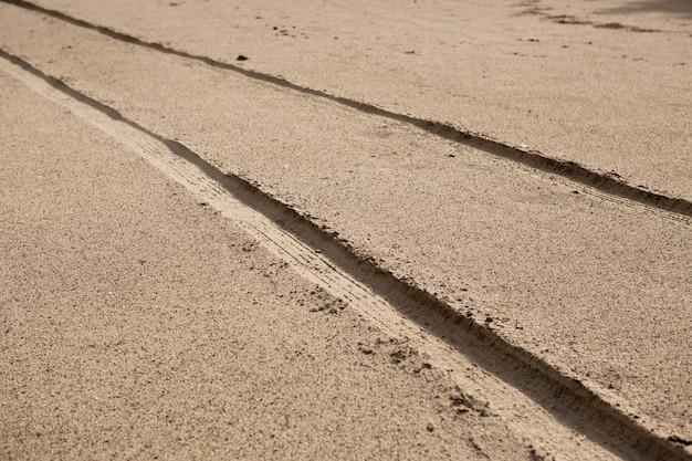 Ślady opon samochodowych na piasku plaży w perspektywie.