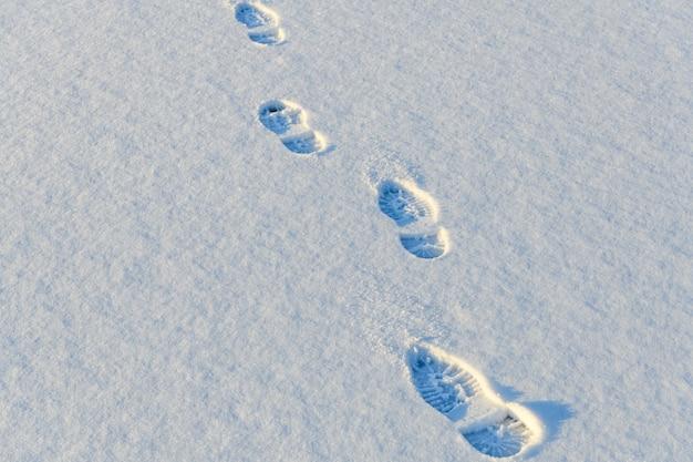 Ślady podeszwy buta na białym śniegu