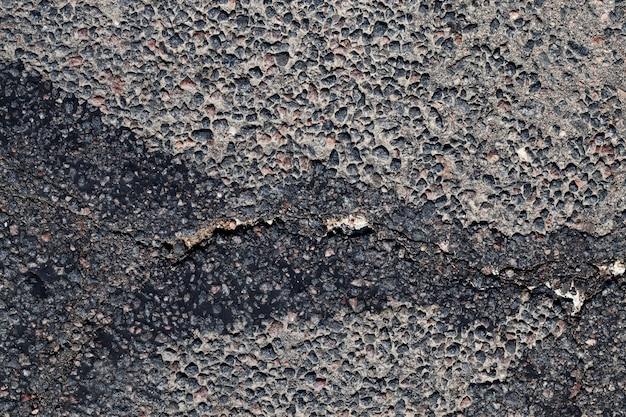 Ślady remontów dróg, fragment drogi asfaltowej z uszkodzeniami i plamami
