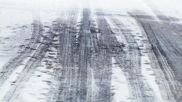 Ślady samochodów na mokrym śniegu, zimowe tło