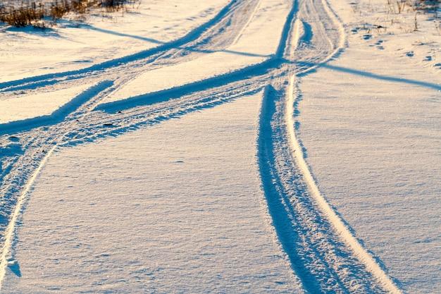Ślady samochodu pozostawionego na śniegu po przejeżdżającym samochodzie.