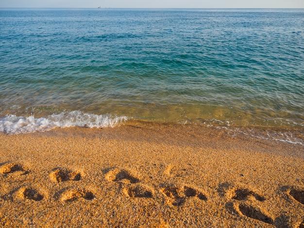 Ślady stóp na piasku morskim. brzeg morski