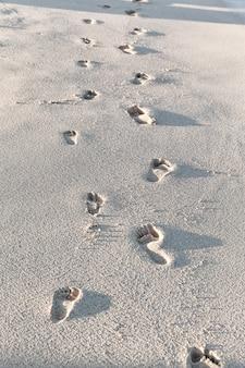 Ślady stóp na piaszczystej plaży w lecie