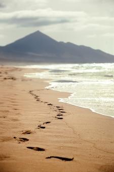 Ślady stóp na piaszczystej plaży z górą w tle na wyspach kanaryjskich, hiszpania