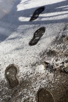 Ślady w teksturze topniejącego śniegu z odciskami butów