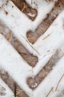 Ślady z bieżnika opony samochodowej na śniegu w sezonie zimowym