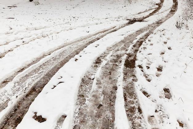 Ślady z kół samochodu na nieutwardzonej wiejskiej drodze pokrytej śniegiem. na śniegu są ślady stóp.