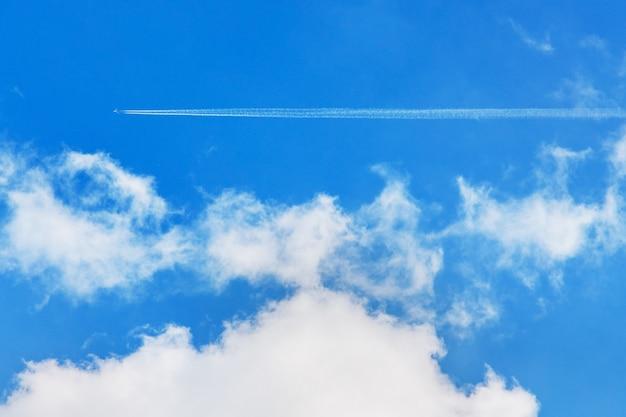 Ślady z samolotu nad białymi chmurami na niebieskim niebie