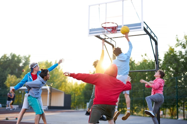 Slam dunk. młodzi koszykarze rasy kaukaskiej, chłopcy rzucający piłkę do kosza do koszykówki