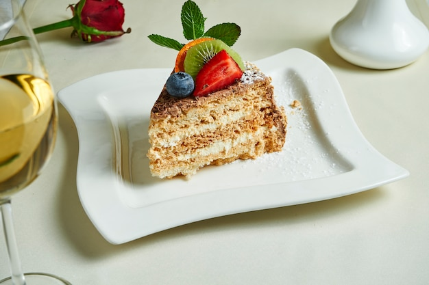 Sławny tradycyjny kijowski tort na białym talerzu (hazelnut daquoise ciasto). smaczne warstwy bezy i waniliowy deser maślany. jedzenie leżało płasko