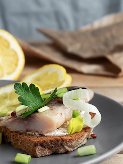 Śledź kanapkowy w occie, podawany z cebulą, natką pietruszki i cytryną.