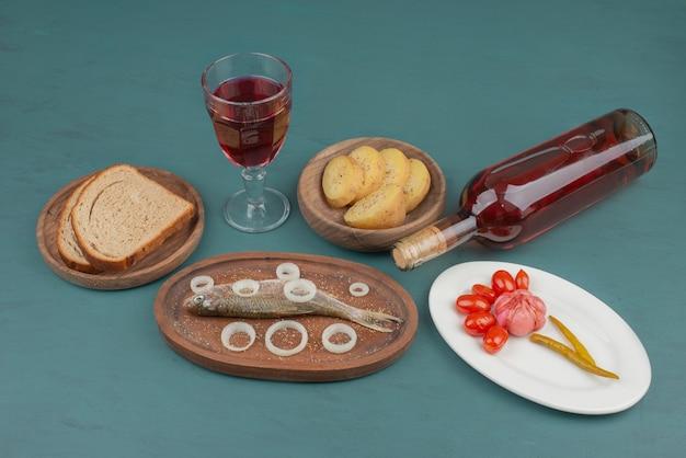 Śledź, kromki chleba, ziemniaki gotowane, talerz pikli i kieliszek wina na niebieskiej powierzchni.