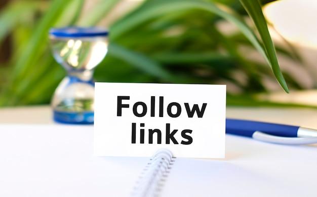 Śledź linki ze strony internetowej - tekst koncepcji biznesowej na białym notatniku i zegarze z klepsydrą, zielone liście kwiatów