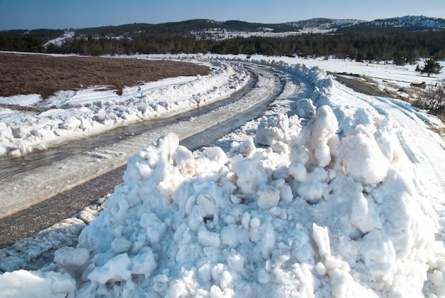 Śledź na zimowej drodze z głębokim śniegiem.