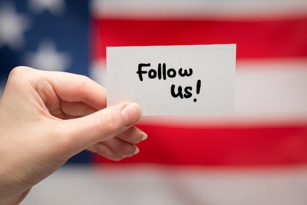 Śledź nas tekst na karcie. tle flagi amerykańskiej.