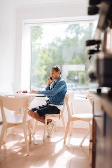 Śledź swój biznes. poważny młody człowiek siedzi w kawiarni i wpatruje się w swojego laptopa