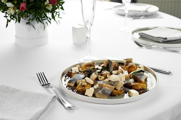Śledź z ziemniakami z bliska, na stole z białym obrusem, marynowany śledź z dodatkiem jako przystawka na bankiecie.