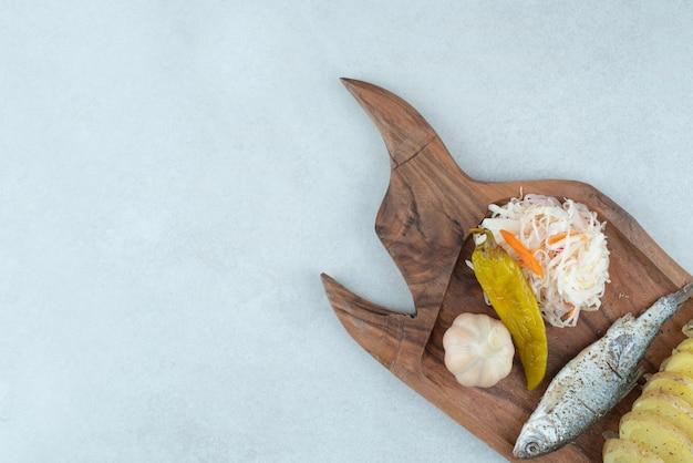 Śledź, ziemniaki gotowane i marynaty na desce.