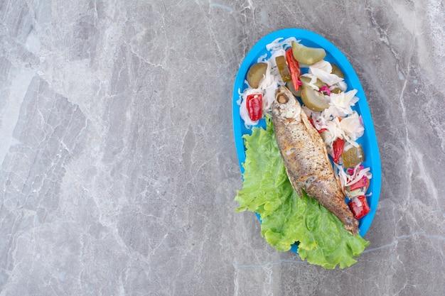 Śledzie i marynowane warzywa na niebieskim talerzu.