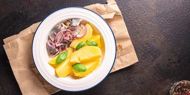 Śledzie ziemniaki marynowana ryba z cebulą świeża porcja gotowa do spożycia przekąska na stole