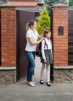 Śliczna 10-letnia dziewczyna w mundurze idzie do szkoły z domu