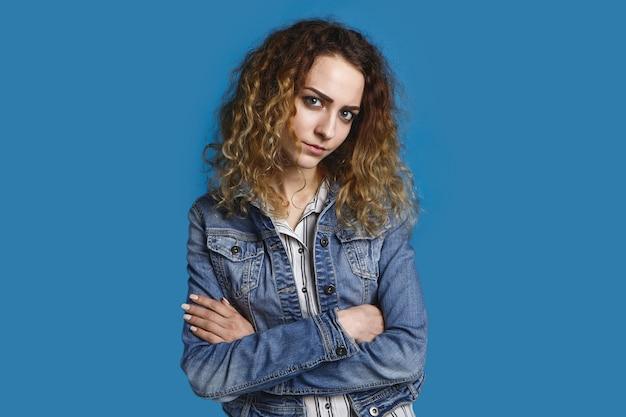 Śliczna 20-letnia dziewczyna z luźnymi kręconymi włosami, pozująca podejrzanie i nieufnie, z założonymi rękoma, w stylowej dżinsowej kurtce. wyraz twarzy, emocje i mowa ciała