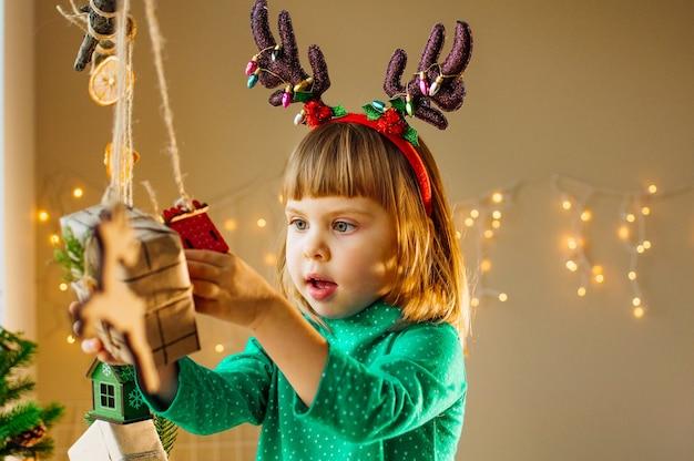 Śliczna 3-letnia dziewczynka bawi się świąteczną girlandą ozdobioną drewnianymi zabawkami i pudełeczkami na prezenty. selektywna ostrość.