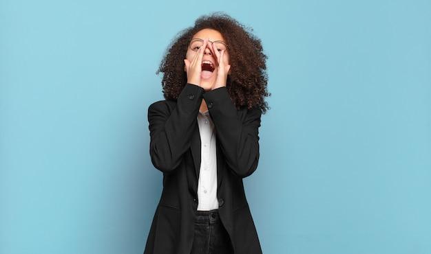 Śliczna afro nastolatka czuje się szczęśliwa, podekscytowana i pozytywna, wydając wielki okrzyk z rękami przy ustach, wołając. humorystyczna koncepcja biznesowa