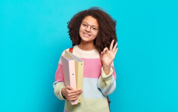 Śliczna afro nastolatka czuje się szczęśliwa, zrelaksowana i usatysfakcjonowana, okazując aprobatę dobrym gestem, uśmiechając się. koncepcja studenta
