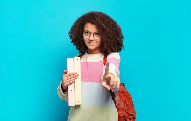 Śliczna afro nastolatka uśmiechająca się dumnie i pewnie wykonując triumfalna pozę numer jeden, czując się jak lider. koncepcja studenta