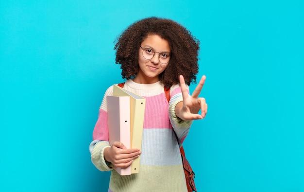 Śliczna afro nastolatka uśmiechnięta i wyglądająca na szczęśliwą, beztroską i pozytywną, jedną ręką gestykulującą zwycięstwo lub pokój. koncepcja studenta