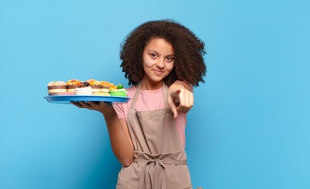 Śliczna afro nastolatka wskazująca z zadowolonym, pewnym siebie, przyjaznym uśmiechem, wybierająca ciebie. humorystyczna koncepcja piekarza