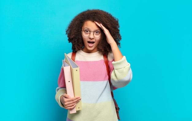 Śliczna afro nastolatka wyglądająca na szczęśliwą, zdziwioną i zaskoczoną, uśmiechniętą i uświadamiającą sobie niesamowite i niewiarygodnie dobre wieści. koncepcja studenta