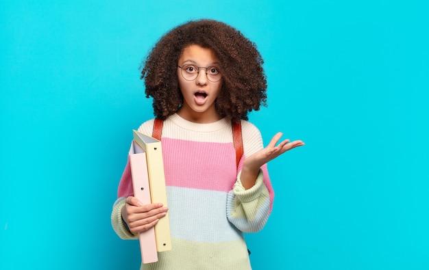 Śliczna afro nastolatka z otwartymi ustami, zdumiona, zszokowana i zdumiona niewiarygodną niespodzianką. koncepcja studenta