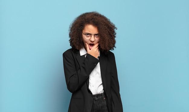 Śliczna afro nastolatka z szeroko otwartymi ustami i oczami iz ręką na brodzie, czuje się nieprzyjemnie zszokowana, mówiąc co lub wow. humorystyczna koncepcja biznesowa