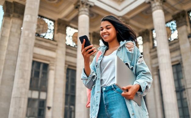 Śliczna afroamerykanka studentka używa smartfona z plecakiem i laptopem w pobliżu kampusu.