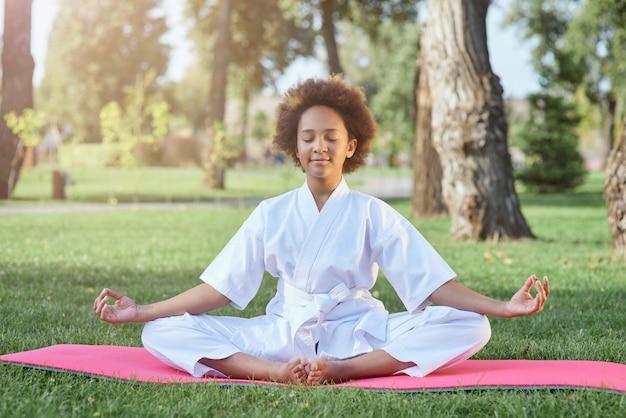 Śliczna afroamerykańska dziewczyna w kimonie karate medytująca na świeżym powietrzu
