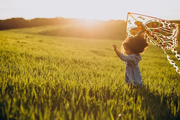 Śliczna afrykańska dziewczynka na polu o zachodzie słońca bawi się latawcem