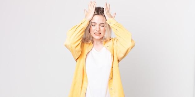 Śliczna albinoska czuje się zestresowana i niespokojna, przygnębiona i sfrustrowana z bólem głowy, podnosząc obie ręce do głowy