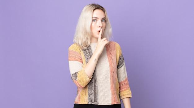 """Śliczna albinoska prosząca o ciszę i spokój, gestykulująca palcem przed ustami, mówiąca """"ćśśśśśś"""" lub dochować tajemnicy"""