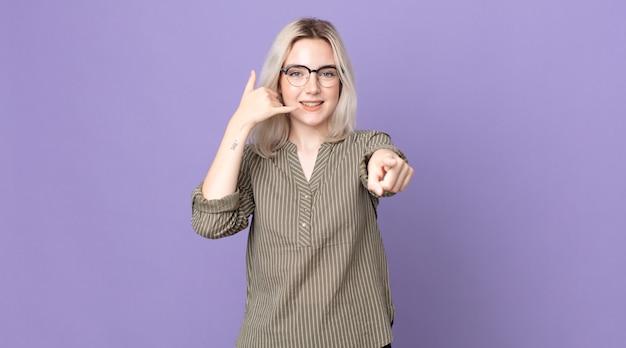 Śliczna albinoska uśmiecha się radośnie i wskazuje na kamerę podczas nawiązywania połączenia, a później gestykuluje, rozmawiając przez telefon